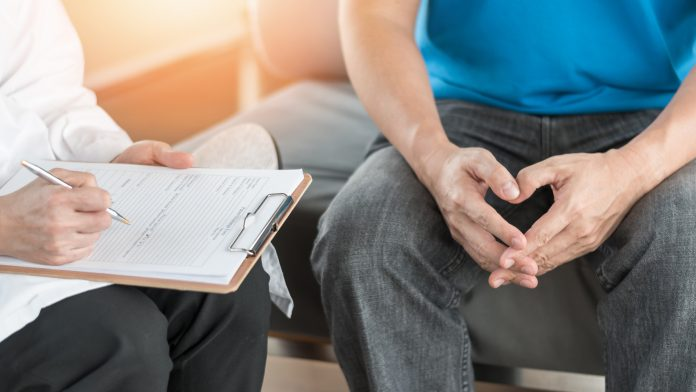 A patient having consultation with doctor or psychiatrist who working on diagnostic examination on men's health disease or mental illness in medical clinic or hospital mental health service center. Photo Courtesy: © 2019 - 2020 Fotolia/Adobe