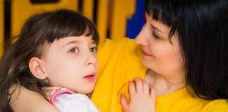 Portrait of little girl in her mother's arms. Courtney Fotolia/Myroslava