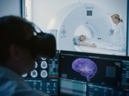 In Medical Control Room Doctor Wearing Virtual Reality Headset Monitors Patient Undergoing MRI or CT Scan Procedure. Computer Displays Show 3D Brain Model with Cancer.