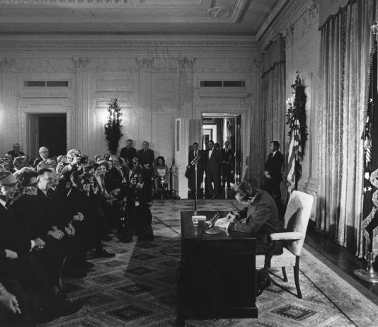 The Signing the National Cancer Act. President Richard Nixon signs the National Cancer Act on December 23, 1971. This is a formal setting with a row of senators visible and some other officials and dignitaries. Courtesy: National Cancer Institute, an agency part of the National Institutes of Health (ID 1935) / Linda Bartlett